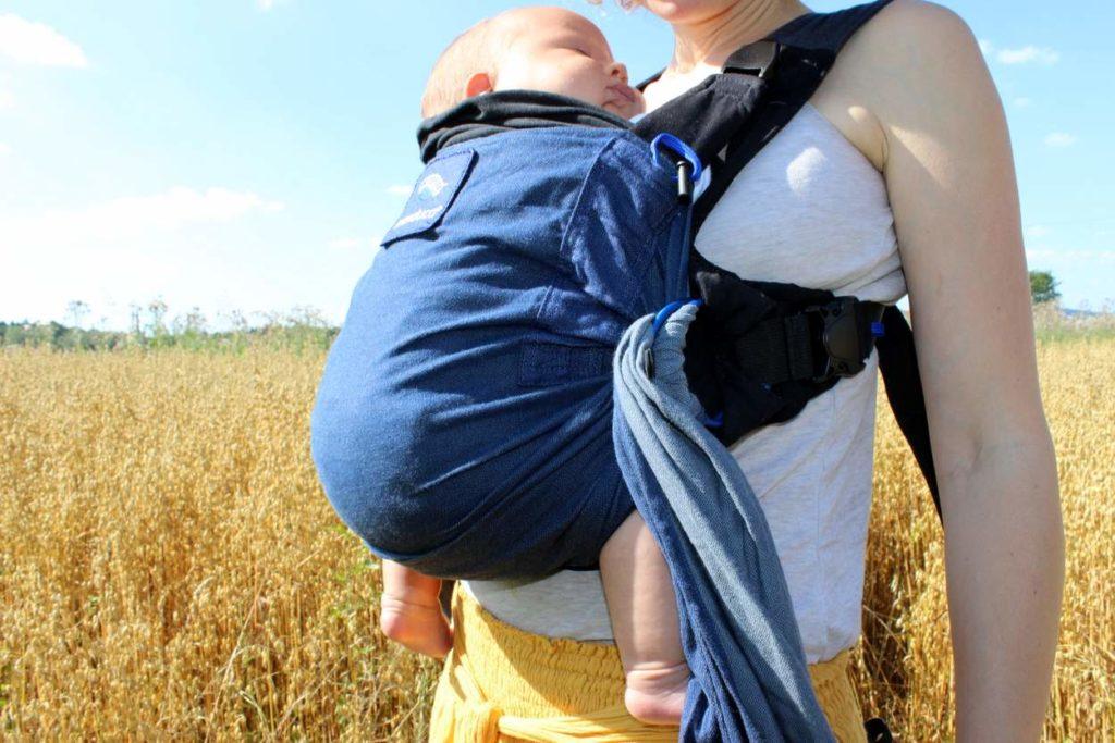Neugeborenes Baby schläft in blauer Manduca Duo Babytrage