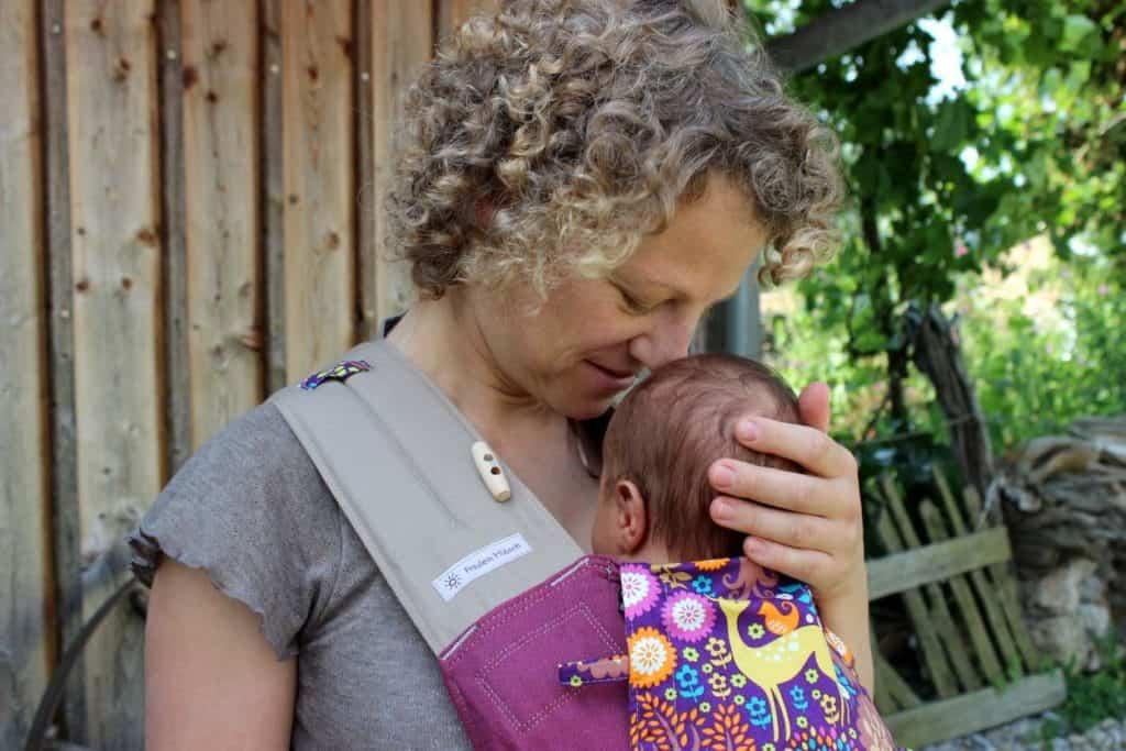 Mutter mit Fräulein Hübsch Babysize Trage und neugeborenem Säugling